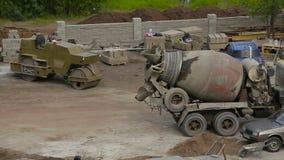 Trabajos de construcción de carreteras con la máquina del compresor del rodillo y la acabadora del asfalto metrajes