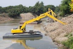 Trabajos de grupo de la máquina del excavador en el río Fotografía de archivo