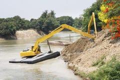 Trabajos de grupo de la máquina del excavador en el río Imagenes de archivo