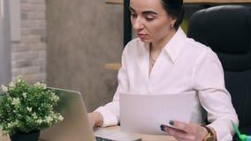 Trabajos de la mujer joven con los documentos en oficina