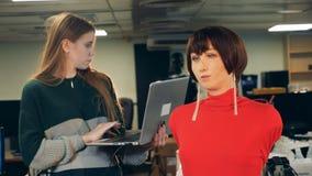 Trabajos de la robótica del científico con un cyborg mientras que mecanografía en un ordenador portátil, cierre para arriba almacen de metraje de vídeo