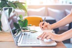 Trabajos de mano de la mujer en un ordenador portátil y una escritura en ingenio de la libreta Foto de archivo libre de regalías