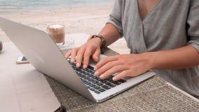 Trabajos de manos femeninos sobre el ordenador portátil en el café al aire libre, tiro giratorio del estabilizador de la cámara almacen de metraje de vídeo