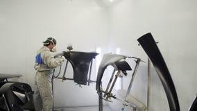 Trabajos de pintura en la cabina del servicio del coche, trabajador de sexo masculino del pintado con pistola metrajes