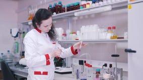 Trabajos del científico con los líquidos en laboratorio metrajes