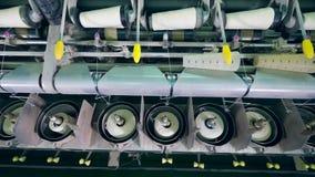 Trabajos del equipo que arrollan con la fibra blanca en una fábrica de la materia textil almacen de metraje de vídeo