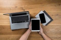 Trabajos del hombre usando los dispositivos digitales Sobre vista del espacio de trabajo de escritorio imagenes de archivo