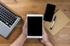 Trabajos del hombre usando los dispositivos digitales Sobre vista del espacio de trabajo de escritorio fotos de archivo