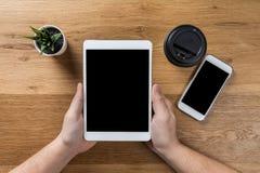 Trabajos del hombre usando los dispositivos digitales Sobre vista del espacio de trabajo de escritorio imagen de archivo libre de regalías