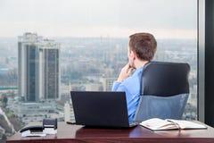 Trabajos duros del encargado en la oficina en el edificio del último piso al lado de la ventana Fotos de archivo