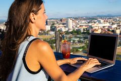 Trabajos femeninos sobre un ordenador portátil en un café en el tejado de una alta subida con una vista panorámica hermosa de la  fotografía de archivo