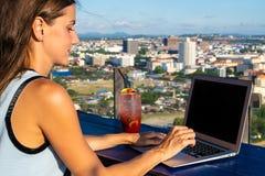 Trabajos femeninos sobre un ordenador portátil en un café en el tejado de una alta subida con una vista panorámica hermosa de la  foto de archivo