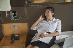 Trabajos múltiple de la empresaria en su cama, al sonreír del teléfono Foto de archivo