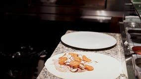 Trabajos múltiple del cocinero El cocinero rellena la pizza cruda y corta el focacci listo metrajes