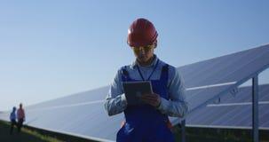 Trabalhador étnico no capacete de segurança usando a tabuleta entre os painéis solares filme