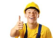 Trabalhador alegre novo que mostra o polegar acima do sinal foto de stock royalty free