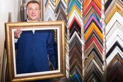 Trabalhador alegre que guarda moldar de quadro da imagem de madeira Fotografia de Stock