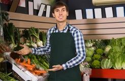 Trabalhador amigável do mantimento no mercado local Imagem de Stock