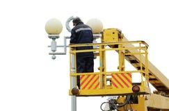 Trabalhador bonde isolado que repara os fios no polo com a ajuda do carro do elevador Fotografia de Stock