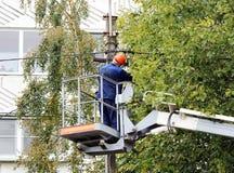 Trabalhador bonde que repara os fios no polo com a ajuda do carro do elevador Foto de Stock