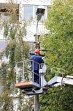 Trabalhador bonde que repara os fios no polo com a ajuda do carro do elevador Foto de Stock Royalty Free