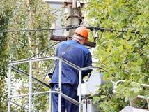 Trabalhador bonde que repara os fios no polo com a ajuda do carro do elevador Fotografia de Stock Royalty Free