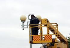 Trabalhador bonde que repara os fios no polo com a ajuda do carro do elevador Imagens de Stock