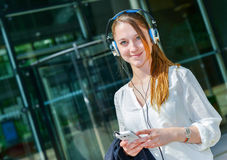Trabalhador bonito que escuta a música na parte dianteira sua empresa Fotografia de Stock Royalty Free