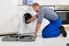 Trabalhador com a caixa de ferramentas que repara a máquina de lavar Fotos de Stock