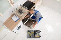 Trabalhador com a caixa de ferramentas que repara a máquina de lavar louça Imagem de Stock