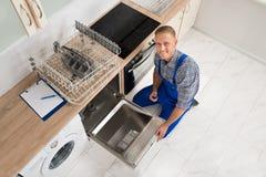 Trabalhador com a caixa de ferramentas que repara a máquina de lavar louça Imagens de Stock Royalty Free