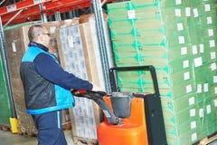 Trabalhador com cardboxes da carga do caminhão de pálete fotografia de stock royalty free