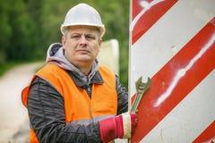 Trabalhador com a chave ajustável na ponte que repara o sinal de estrada Foto de Stock Royalty Free
