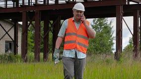 Trabalhador com chave ajustável que anda e que fala no telefone celular vídeos de arquivo
