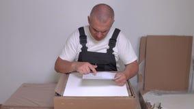 Trabalhador com instrução e caixa da mobília video estoque