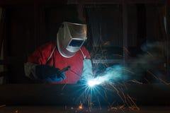 Trabalhador com metal de soldadura da máscara protetora na fábrica fotografia de stock