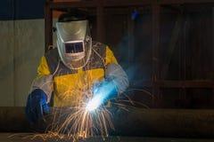 Trabalhador com metal de soldadura da máscara protetora na fábrica imagens de stock royalty free