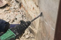 Trabalhador com o martelo bonde que limpa a parede de tijolo vermelho foto de stock