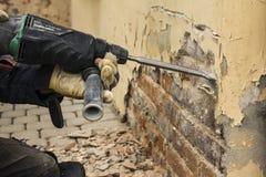 Trabalhador com o martelo bonde que limpa a parede de tijolo vermelho fotos de stock royalty free