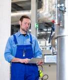 Trabalhador com o tablet pc na planta industrial foto de stock royalty free