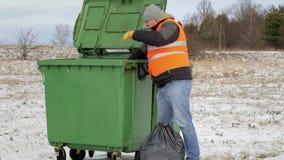 Trabalhador com os sacos de lixo perto do recipiente video estoque