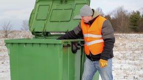 Trabalhador com os sacos de lixo perto do recipiente no inverno filme