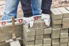 Trabalhador com pavimentação de tijolos imagem de stock
