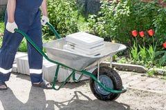 Trabalhador com um wheelbarrow Fotografia de Stock