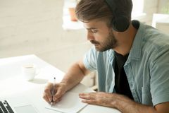 Trabalhador concentrado nos fones de ouvido que olha a importação notando webinar fotos de stock royalty free