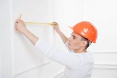 Trabalhador considerável novo no capacete com medição Fotografia de Stock