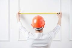 Trabalhador considerável novo no capacete com medição Imagens de Stock Royalty Free