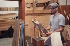 Trabalhador da carpintaria que olha o detalhe de madeira imagem de stock