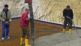 Trabalhador da construção ao concreting uma construção da laje da base da fundação filme