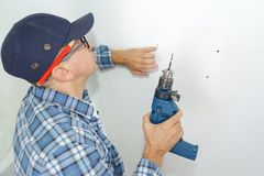 Trabalhador da construção aproximadamente para furar a parede foto de stock